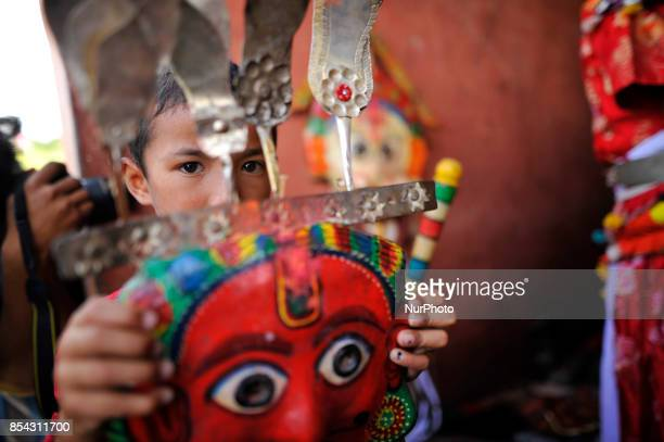 A Nepalese kid hold his grandfather's deity mask during the celebration of Shikali Festival at Khokana Village Patan Nepal on Tuesday September 26...