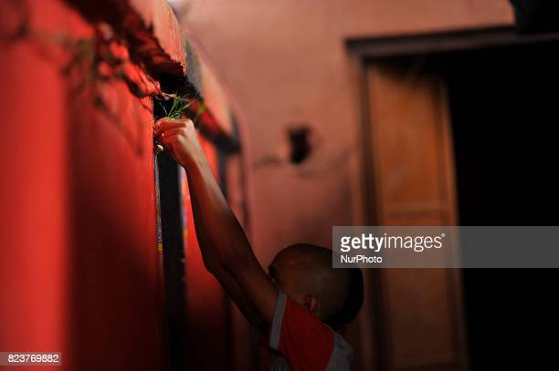 Nepalese kids from Hindu school Bhagwat Sanyaas Aashram Gurukul sticks a picture of a snake god at the main entrance during Nag Panchami festival at...