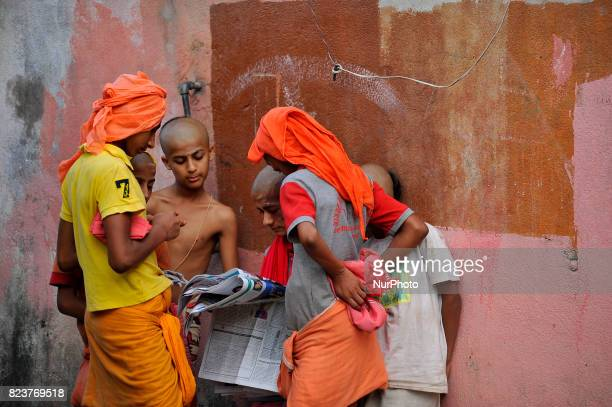 Nepalese kids from Hindu school Bhagwat Sanyaas Aashram Gurukul reading daily newspaper at Pashupatinath Temple Kathmandu Nepal on Friday July 28 2017