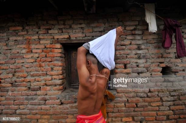 Nepalese kids from Hindu school Bhagwat Sanyaas Aashram Gurukul take off cloth for performing rituals offering during Janai Purnima festival or...