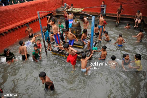 Nepalese kids jump and play on the water collected in Kumbheshwor temple on during Janai Purnima festival or Rakchhya Bandhan at Patan Nepal on...