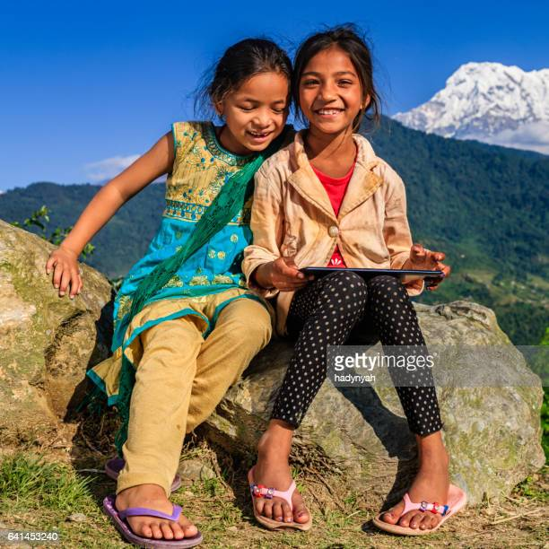 Nepalese little girls using digital tablet, Annapurna Range on background
