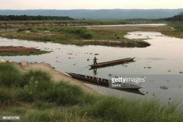 nepalese local man traveling by boat on a rapti river in a national park chitwan - chitwan stock pictures, royalty-free photos & images