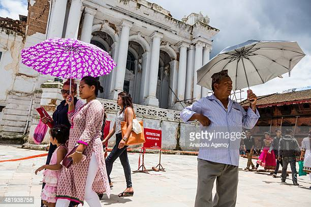 Nepalese locals walk with umbrellas shielding themselves from the sun in Durbar square in Kathmandu on July 25, 2015. Today marks the 3 month...