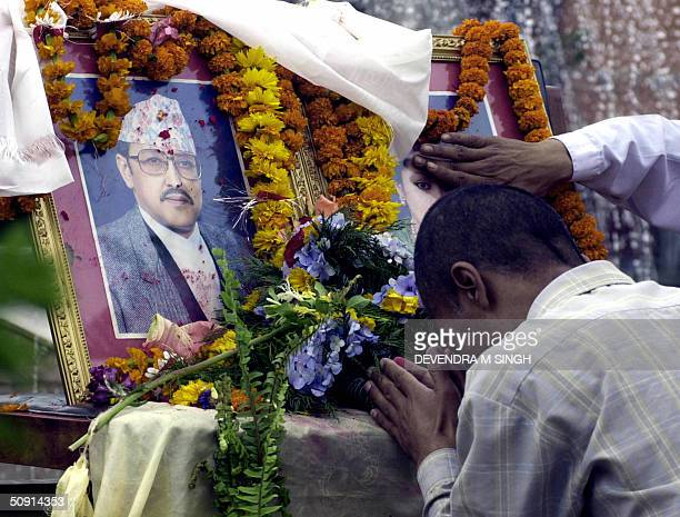 Nepalese man bows his head in prayer at an altar adorned with garlanded photographs of the late King Birendra and Queen Aishwarya at Patan Kathmandu...