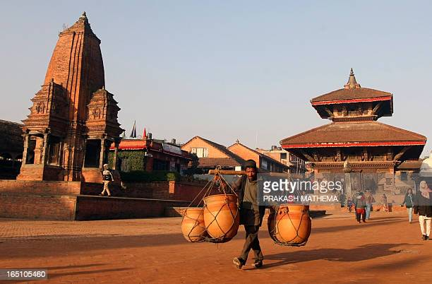 A Nepalese man carries clay pots through the Bhaktapur Durbar Square in Bhakatpur some of 12 kilometers southeast of Kathmandu on February 18 2011...