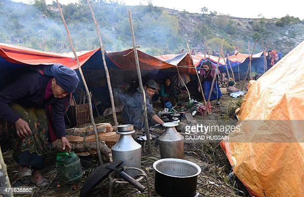A Nepalese man cooks food outside makeshift tents at Laprak village in northerncentral Gorkha district on April 30 2015 The UN launched an appeal for...