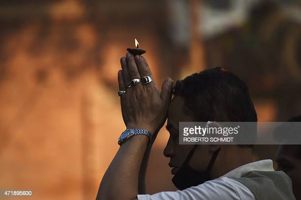 A Nepalese man holds lit wick over his head as he offers a prayer in front of a statue of Hindu diety Kaal Bhairab in the Durbar Square neighbourhood...