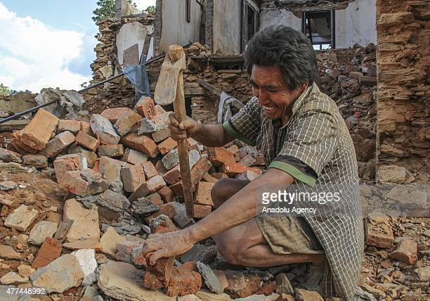 Nepalese man is seen on the debris of a collapsed building in the Sindhupalchowk district of Nepal on June 17 2015 Rubble of buildings hasn't been...