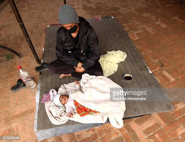 Nepalese man looks after his three-month-old baby at a makeshift camp in Bhaktapur on the outskirts of the capital city of Kathmandu on April 29,...