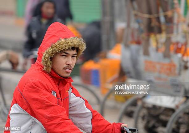 A Nepalese man rides his bicycle on a cold morning in Chitwan some 150 km south of Kathmandu on January 5 2012More then 10 people die due to cold...
