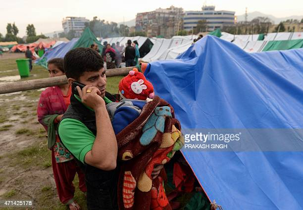 A Nepalese man talks on a phone at a camp set up in the wake of a devastating earthquake in Kathmandu on April 28 2015 Hungry and desperate villagers...