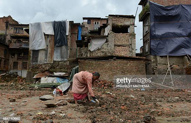A Nepalese man works in near earthquakedamaged houses in Bhaktapur on the outskirts of Kathmandu on August 21 2015 Twin earthquakes which struck the...