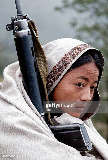 Nepalese Maoist guerrilla woman holds a rifle while watching an armed exercise in Bhojpur eastern Nepal 08 November 2005 Nepal's Maoist rebels...