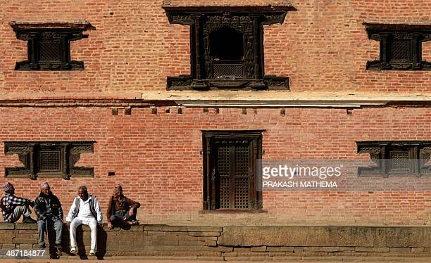 Nepalese men sit at an open area at the Bhaktapur Durbar Square area in Bhaktapur some 12 kilometres southeast of Kathmandu on February 6 2014...