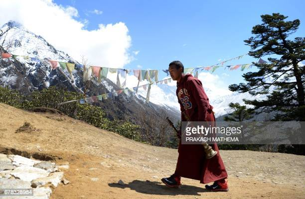 A Nepalese monk walks towards the cremation site of Swiss climber Ueli Steck at Tengboche some 300 kms northeast of Kathmandu on May 4 2017 The body...