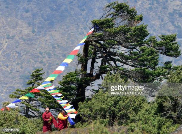 Nepalese monks hang prayer flags as they prepare for the cremation of Swiss climber Ueli Steck at Tengboche some 300 kms northeast of Kathmandu on...