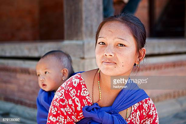 nepalese mother carrying her baby on the back near kathmandu. - nepalese ethnicity stock pictures, royalty-free photos & images