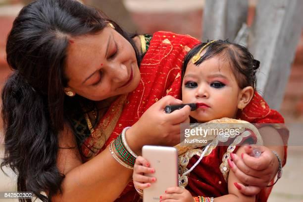 A Nepalese mother puts lipstick on her daughter's mouth during celebration of Kumari puja at Basantapur Durbar Square Katmandu Nepal on Monday...