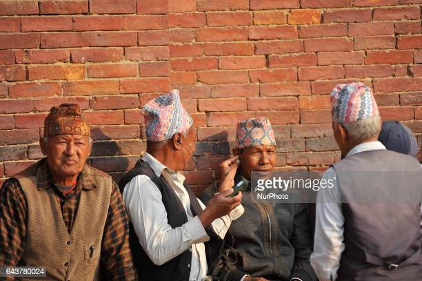 Nepalese old Man checking the sound of mobile phone at the premises of the Patan Durbar Square Patan Nepal on Wednesday February 22 2017