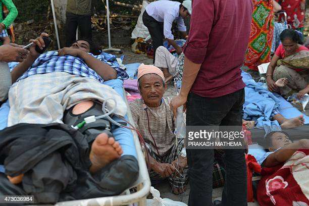 Nepalese patients lie on stretchers in an open area after being carried out of a hospital building as a 73 magnitude earthquake hits the country in...