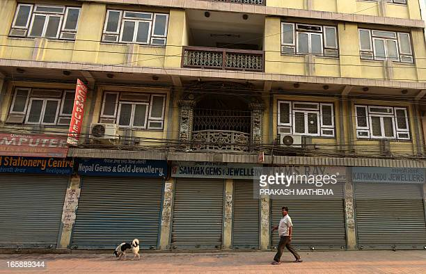 A Nepalese pedestrian walks past shuttered shops during a general strike called by the Communist Party of NepalMaoist in Kathmandu on April 7 2013...