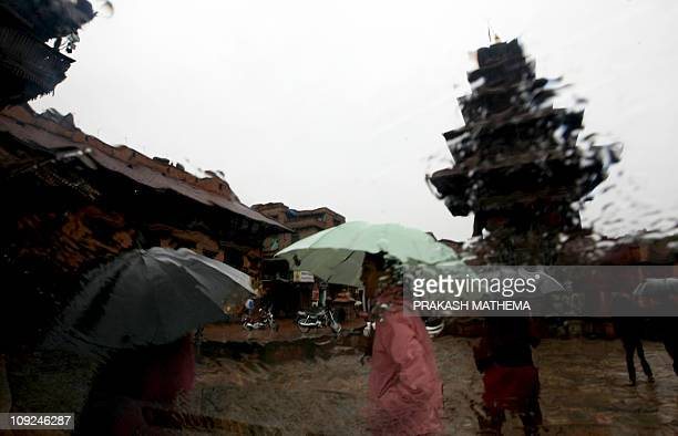 Nepalese pedestrians are seen through the windscreen of a vehicle as they ealk through a downpour in Bhaktapur some 12 kms southeast of Kathmandu on...