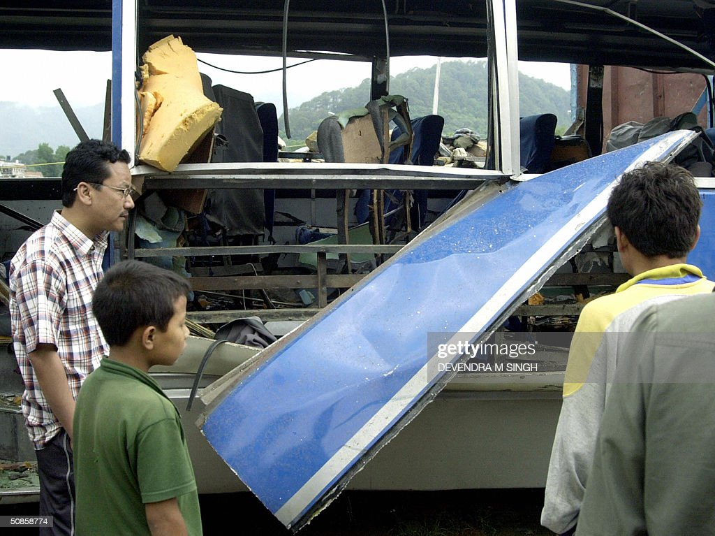 Nepalese pedestrians look at the wreckage of a bomb dmaged bus in Kathmandu, 20 May 2004. Maoist rebels are suspected of planting the device which exploded on the third day of a nationwide general strike, destroying the bus but injuring no-one.