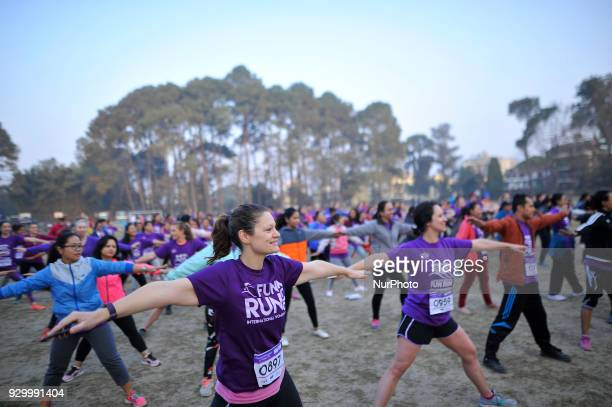Nepalese people and foreigners warm up themselves before running on an International Women's Day 5K Fun Run at Patan Nepal on Saturday March 10 2018...