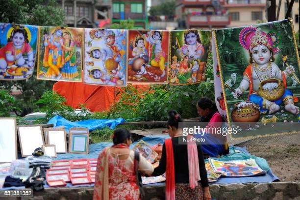 Nepalese people buying the poster of Lord Krishna during Krishna Janmashtami Festival celebrated at Kathmandu Nepal on Monday August 14 2017 Krishna...