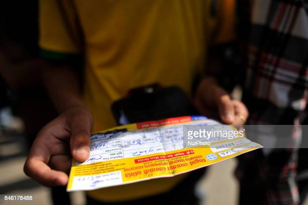 Nepalese People check the tickets after waits in queue for the upcoming Biggest Dashain Festival celebration at New Bus park Kathmandu Nepal on...