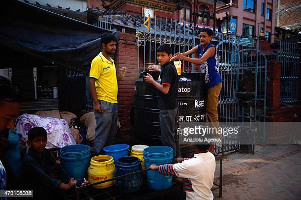 Nepalese people fill their buckets with water following the second major earthquake in Kathmandu, Nepal on May 13, 2015. The second major earthquake...