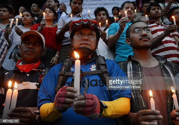 Nepalese people holds candles in memory of the 16 Nepalese Sherpa guides killed in an avalanche on Mount Everest in Katmandu on April 30 2014 An...