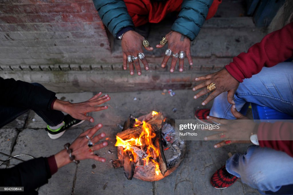 Nepalese people keep warm themselves by making fire during cold weather at Basantapur Durbar Square, Kathmandu, Nepal on Friday, January 12, 2018.