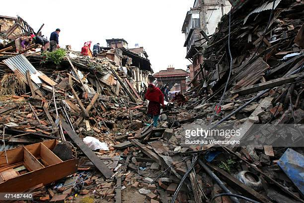 Nepalese people look for their belongings among the rubble of their destroyed homes on April 29 2015 in Kathmandu Nepal A major 78 magnitude...