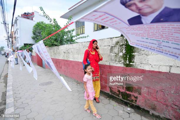 Nepalese people pass as a supporters and well-wisher arranging posters of Former King Gyanendra Shah during on his 71th birthday at his residence...