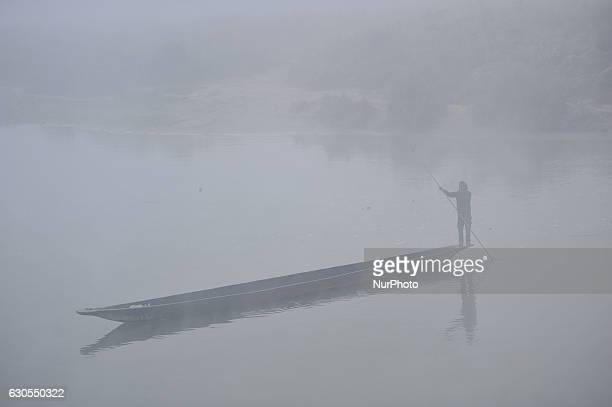Nepalese people row his boat on the Rapti River on the early morning at Sauraha Chitwan Nepal on Monday December 26 2016