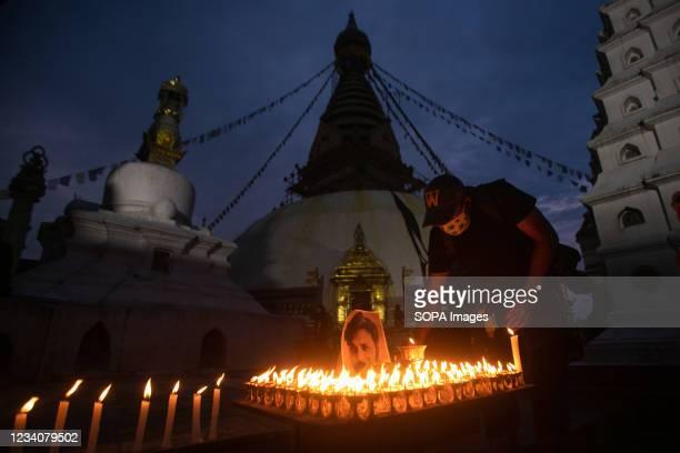 Nepalese Photojournalists lights a candle to pay tribute to Reuters photojournalist Danish Siddiqui, in front of the Swyambhunath Stupa in Kathmandu....