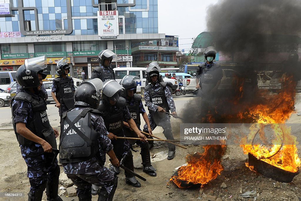Nepalese police attempt to extinguish burning tyres set ablaze by activists demonstrating against the Constitutional Council's appointment of Lokman Singh Karki as Commission for the Investigation of Abuse of Authority chief, in Kathmandu on May 8, 2013. Dozens of rights activists and student organisations have been protesting since the start of the week over the decision to appoint Lokman Singh Karki to run the Commission for the Investigation of Abuse of Authority. AFP PHOTO/ Prakash MATHEMA
