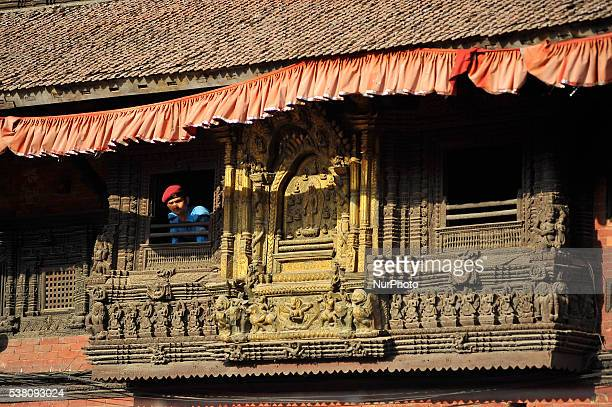 A Nepalese Police man glancing from the old traditional window located at Patan Museum at Patan Durbar Square Patan Nepal on June 04 2016 Patan...