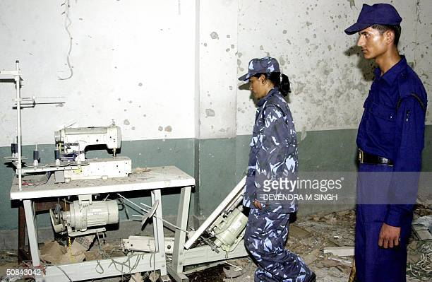 Nepalese police officers inspect a bomb damaged sewing machine following a blast at a garment factory in Kathmandu 16 May 2004 Maoist rebels fighting...