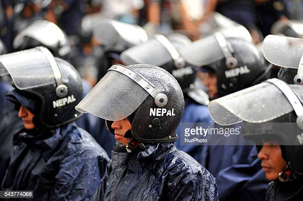 Nepalese police personnel guard on on sudden rainfall during a protest rally to pressurize Government of Nepal for Black marketing, corruption, Price...