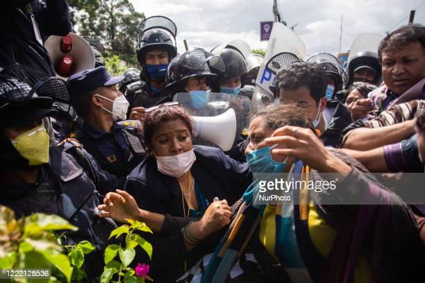 Nepalese police personnel try to stop protesters marching towards main highway in a protest against killing of Dalit low-caste youth in Rukum...
