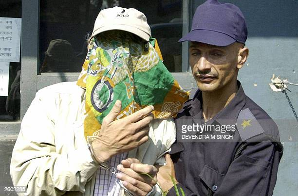 Nepalese policeman escorts convicted criminal and French national Charles Sobhraj his face covered by a handkerchief at the entrance to Kathmandu...