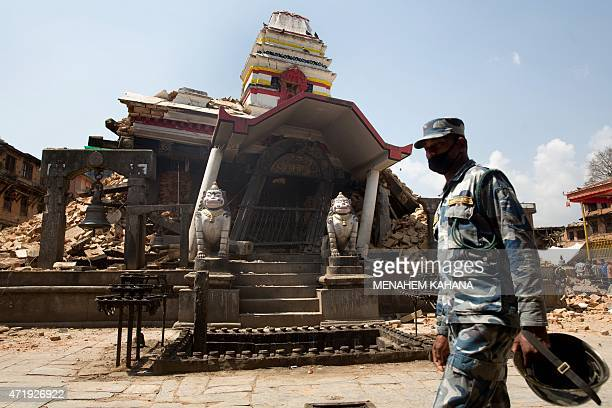A Nepalese policeman walks past the destroyed temple of Rato Machindranath Bahan at Bungamati village in Lalitpur district of the Kathmandu valley on...