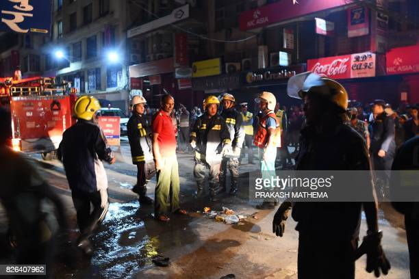 Nepalese policemen and firefighters prepare to douse a fire at a shop in Kathmandu on August 4 2017 / AFP PHOTO / PRAKASH MATHEMA