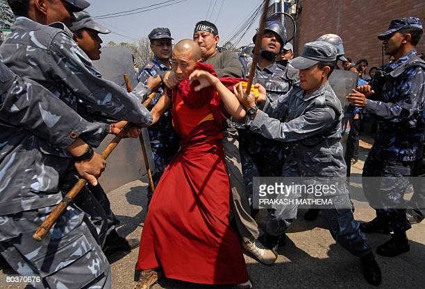 Nepalese policemen arrest a Tibetan monk protester in exile during an antiChinese demonstration in front of the consular section of the Chinese...