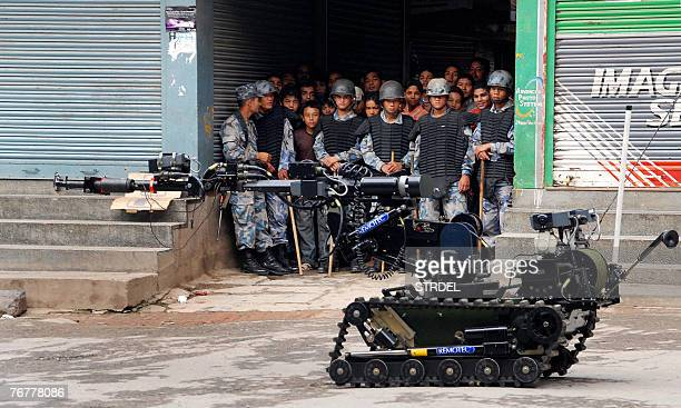 CORRECTION Nepalese policemen keep back onlookers as an army bomb disposal unit uses a robot to investigate a suspicious package left on a motorbike...