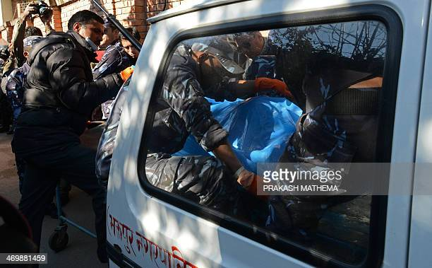 Nepalese policemen move the bodies of victims of an air crash in the country's mountainous western region from an ambulance to the morgue of the...