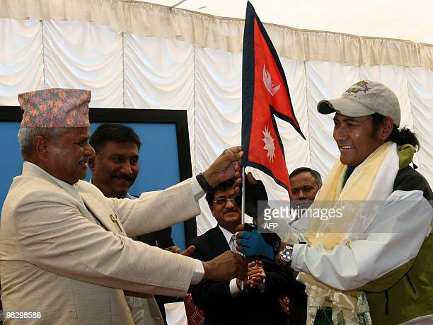 Nepalese President Ram Baran Yadav hands over a Nepalese flag to cyclist Pushkar Shah in Kathmandu on April 7 as he prepares to leave for Mount...